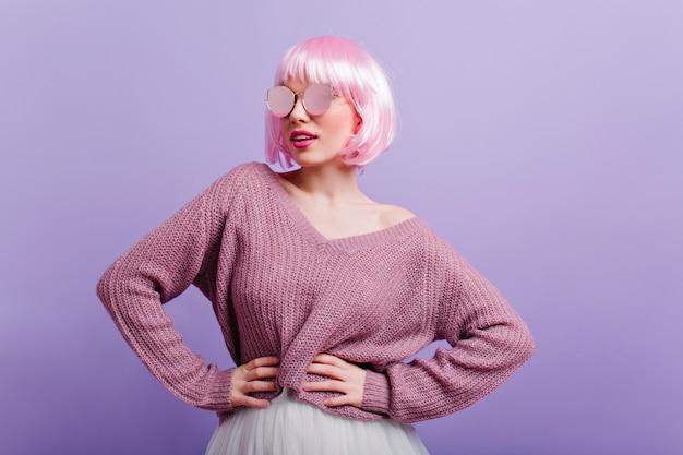 Fröhliches mädchen mit rosa glattem haar, das in der selbstbewussten haltung steht und lächelt. hübsche europäische dame in pullover und funkelnden gläsern, die während des fotoshootings tanzen.