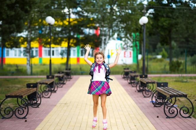 Fröhliches mädchen mit rucksack und schuluniform auf dem schulhof. zurück zur schule
