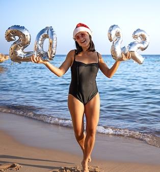 Fröhliches mädchen mit silbernen kugeln in form von zahlen 2022 in der nähe des meereskonzepts von neujahr
