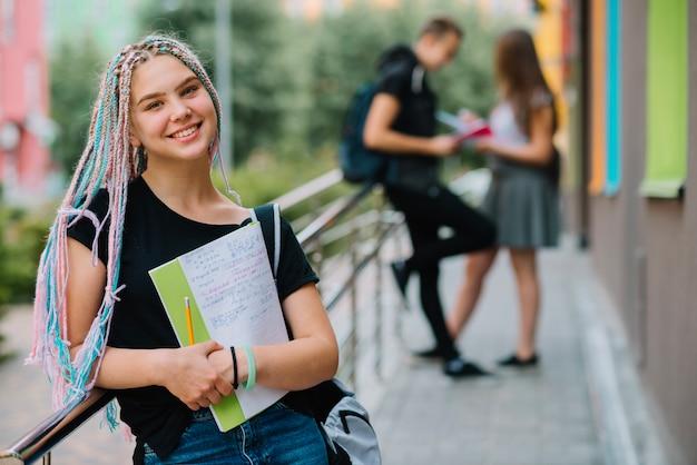 Fröhliches mädchen mit studien posiert draußen