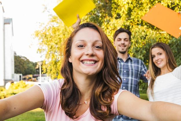 Fröhliches mädchen posiert mit studenten