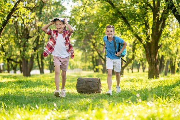 Fröhliches mädchen und junge mit rucksack im park