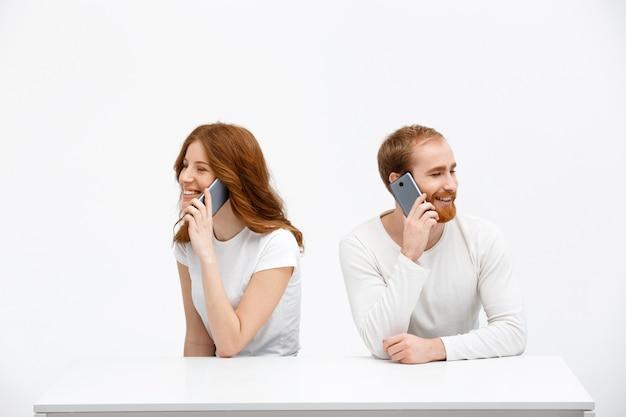 Fröhliches mädchen und mann, die am telefon sprechen, sitzen zusammen