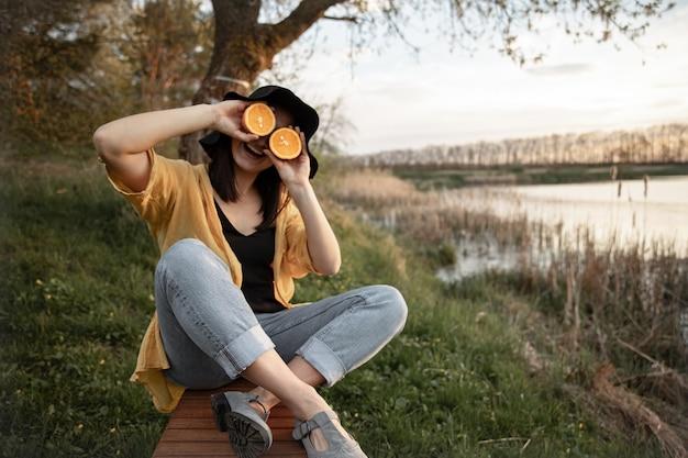 Fröhliches mädchen verzieht das gesicht mit einer frischen orange und ruht in der natur in der nähe des flusses