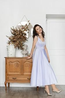 Fröhliches modelgirl in einem eleganten rosa abendkleid und goldenen schuhen