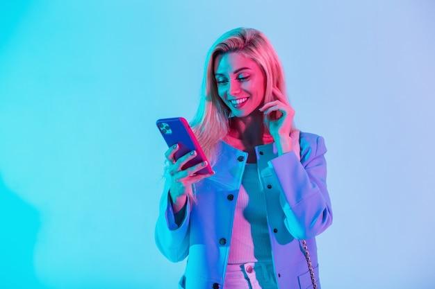 Fröhliches, modisches junges mädchen mit einem schönheitslächeln in modischer, eleganter geschäftskleidung mit einer jacke, die ein smartphone hält und eine nachricht auf einem mehrfarbigen neonrosa licht im studio eingibt