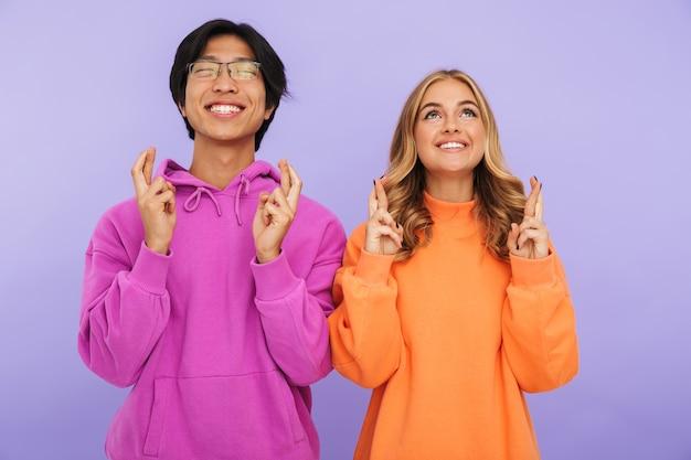 Fröhliches multhiethnisches teenagerpaar, das isoliert zusammensteht