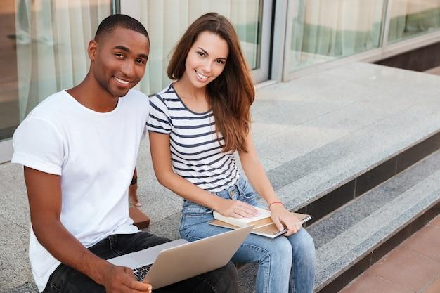 Fröhliches multiethnisches junges paar, das draußen sitzt und laptop benutzt