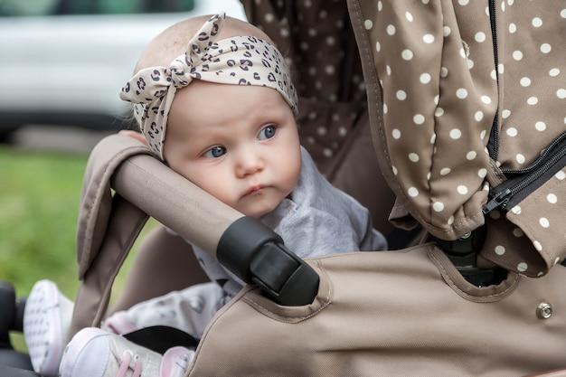 Fröhliches nachdenkliches emotionales acht monate altes blauäugiges mädchen sitzt im kinderwagen auf einem spaziergang und wartet auf mama. kleines und süßes baby mit stirnband auf dem kopf, das im kinderwagen sitzt. konzept der richtigen erziehung und kindheit
