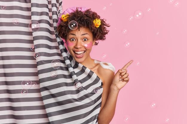 Fröhliches optimistisches junges lockiges afroamerikanisches mädchen steht nackt bedeckt mit seifenblasen und schaum zeigt an, zeigt beiseite kopienraum