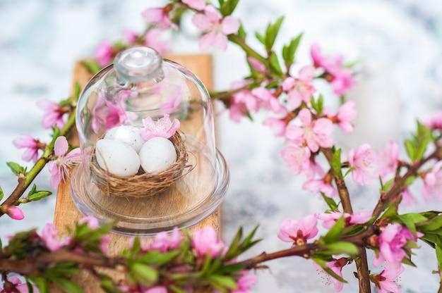 Fröhliches osterkonzept mit eiern und blühendem zweig. frühling, ostern, eier nahaufnahme und kopierraum.