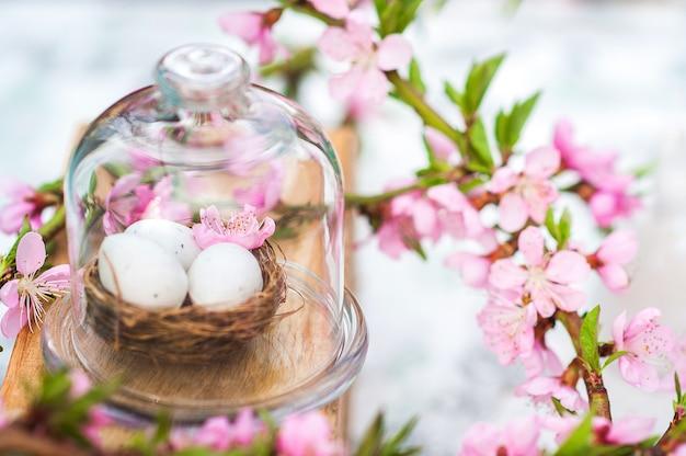 Fröhliches osterkonzept mit eiern und blühendem zweig.
