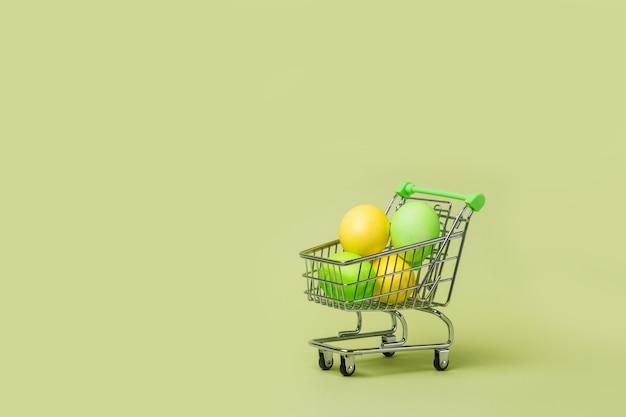 Fröhliches osterkonzept mit ostereiern im supermarktwagen, einkaufswagen.