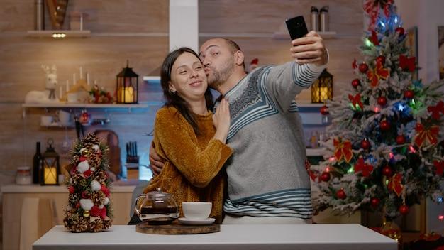 Fröhliches paar beim fotografieren an heiligabend