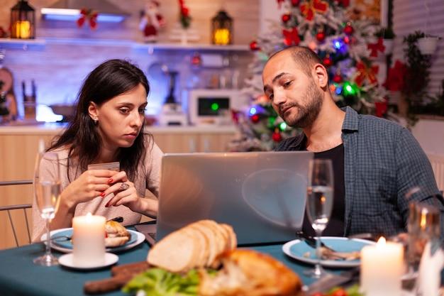Fröhliches paar beim online-shopping weihnachtsgeschenk mit kreditkarte bezahlen