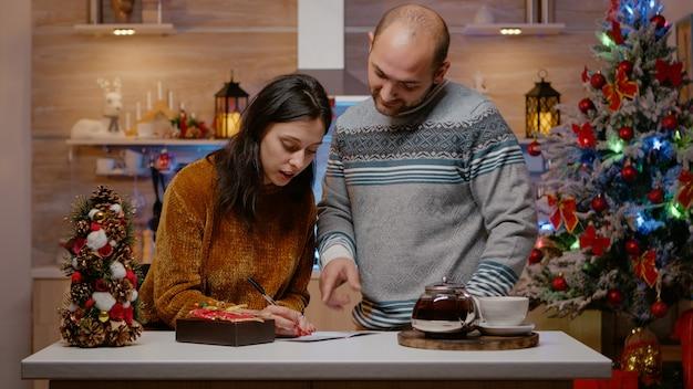 Fröhliches paar bereitet geschenk- und weihnachtskarte vor