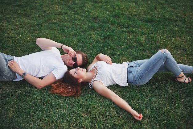 Fröhliches paar, das auf dem gras liegt.