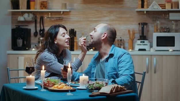 Fröhliches paar, das beim abendessen einen zarten moment verbringt. frau und ehemann beim romantischen essen in der küche, gemeinsames essen zu hause, das feiern ihres jubiläums, überraschungsurlaub bei kerzenlicht surprise
