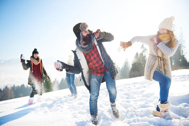 Fröhliches paar, das im schnee spielt