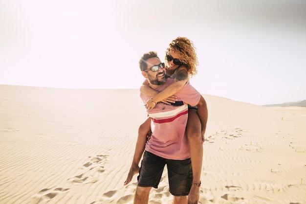 Fröhliches paar, das in den mann verliebt ist, macht die junge schöne frau auf seinem rücken weiter, die auf sand geht