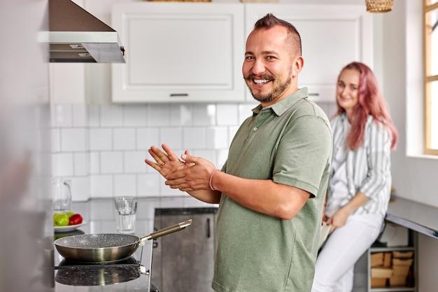 Fröhliches paar, das in der küche kocht, junger mann und frau lachen, kamera schauend. fokus auf männlich