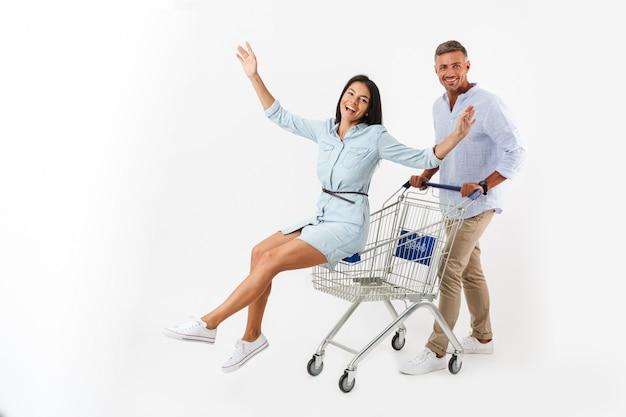 Fröhliches paar, das mit einem einkaufswagen geht