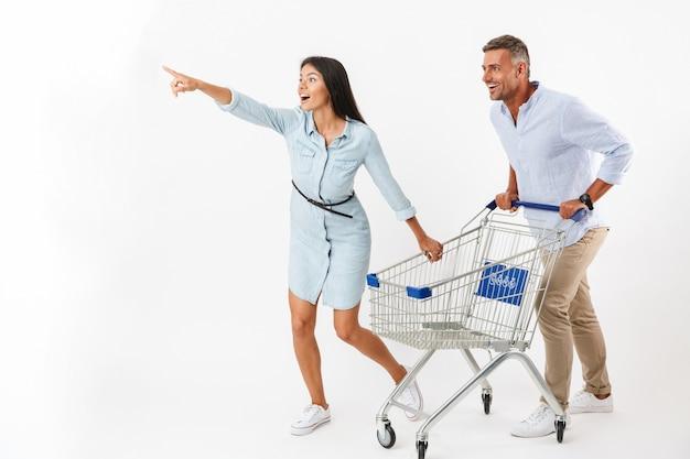 Fröhliches paar, das mit einem einkaufswagen läuft