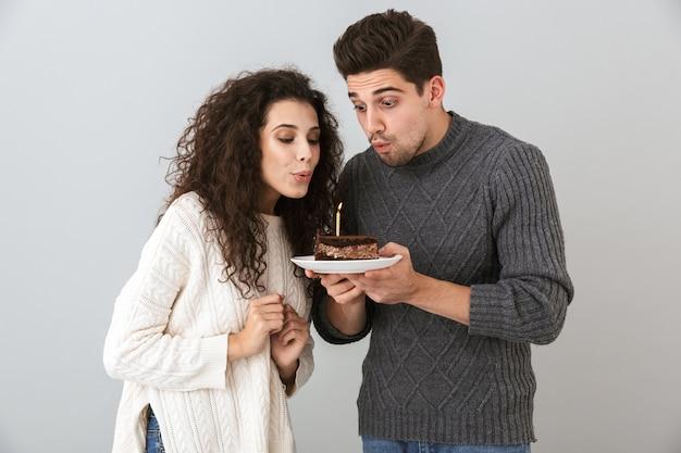 Fröhliches paar, das pullover trägt, die lokal über grauer wand stehen, geburtstag feiern, stück kuchen mit kerze halten