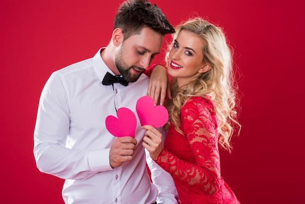 Fröhliches paar, das rosa papierherzen hält