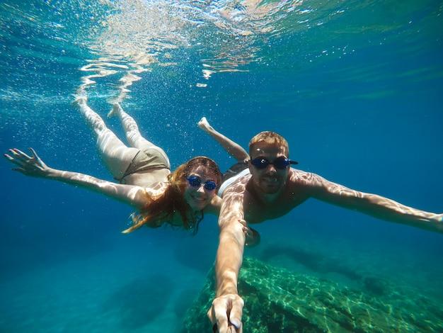 Fröhliches paar, das spaß unter wasser hat und selfie macht.