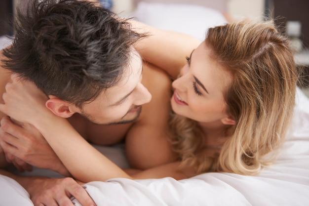Fröhliches paar, das zeit im schlafzimmer verbringt