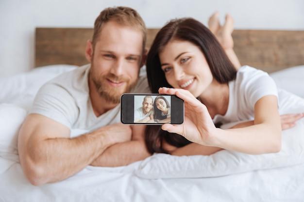 Fröhliches paar, das zusammen im bett liegt und sich mit einem handy fotografiert