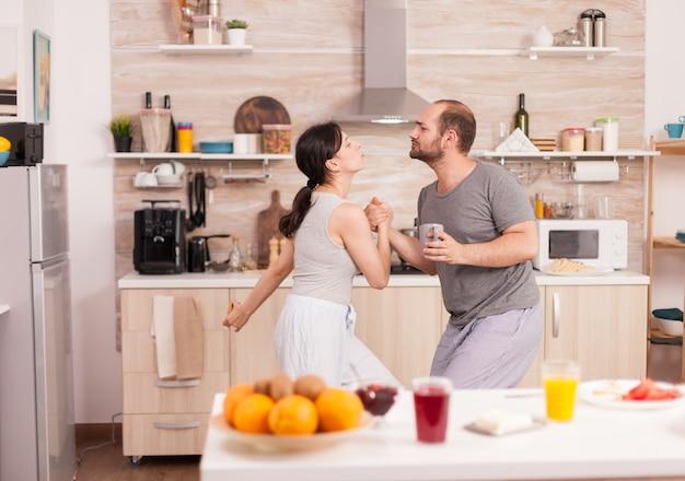 Fröhliches paar im pyjama, das beim frühstück in der küche tanzt und musik hört. unbeschwerter ehemann und ehefrau lachen, singen, tanzen, hören nachdenklich, leben glücklich und sorgenfrei. positive menschen. han