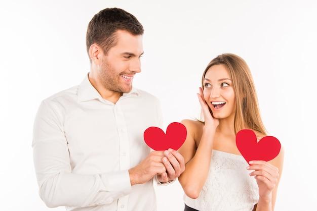 Fröhliches paar in der liebe, die rote papierherzen hält