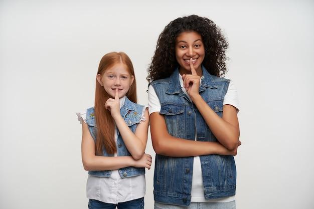 Fröhliches paar junge dunkelhäutige brünette dame und rothaariges langhaariges hübsches mädchen, das zeigefinger auf den lippen hält, darum bittet, geheim zu bleiben und schlau zu lächeln