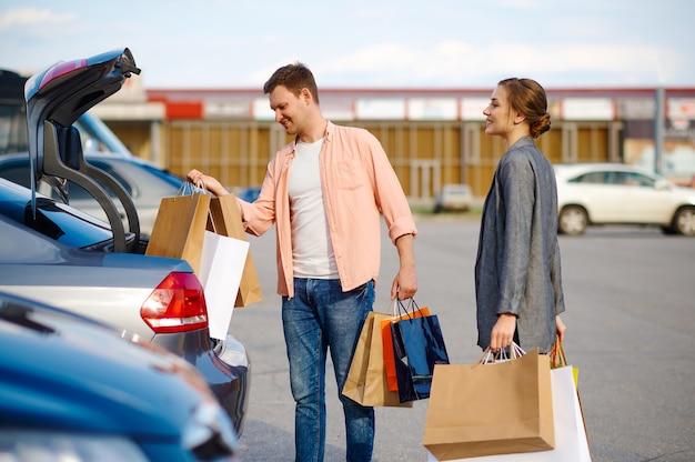 Fröhliches paar legt seine einkäufe in den kofferraum auf dem parkplatz des supermarkts. zufriedene kunden, die einkäufe aus dem einkaufszentrum tragen, fahrzeuge im hintergrund