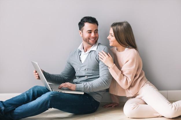 Fröhliches paar mit laptop zu hause. online einkaufen.