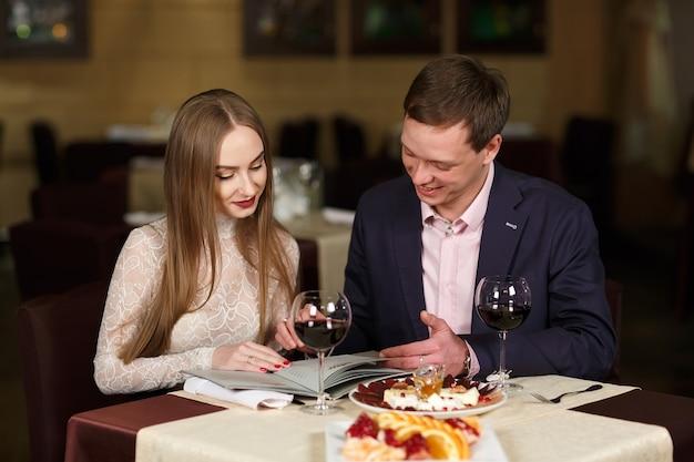 Fröhliches paar mit menü in einem restaurant.
