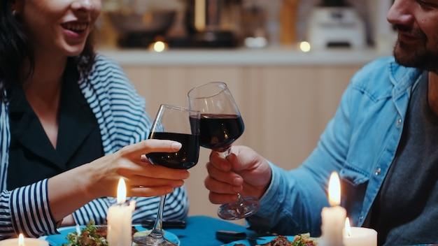 Fröhliches paar mit rotweingläsern sitzt am tisch in der gemütlichen küche. fröhliche verliebte essen gemeinsam das essen, um ihr jubiläum bei kerzenlicht zu feiern