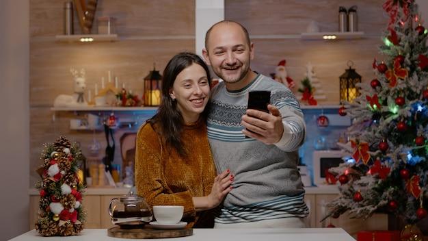 Fröhliches paar mit videoanrufkommunikation auf dem smartphone