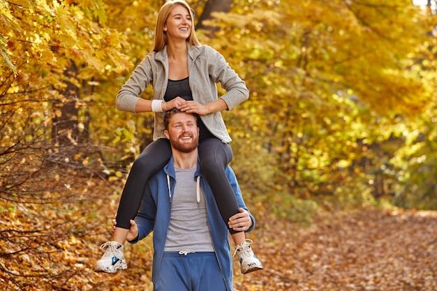 Fröhliches paar verbringt den tag im herbstwald, blonde frau sitzt auf männerhals und lächelt