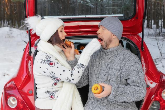 Fröhliches paar verliebt in donuts, die auf dem kofferraum des autos im winterwald sitzen