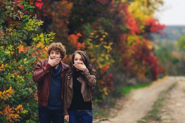 Fröhliches paar zeigt emotionen. mann und frau in lederjacken und jeans zeigen überraschung vor dem hintergrund der herbstbäume.