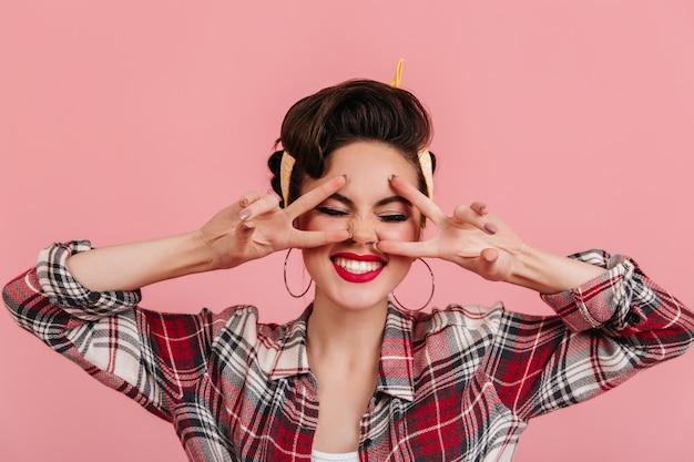 Fröhliches pinup-girl posiert mit geschlossenen augen und lacht. studioaufnahme der ansprechenden jungen frau, die friedenszeichen zeigt.