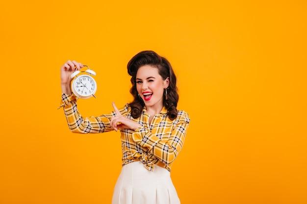 Fröhliches pinup-mädchen, das uhr zeigt. studioaufnahme der glückseligen attraktiven frau lokalisiert auf gelbem hintergrund.