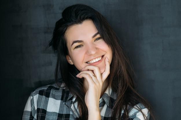 Fröhliches porträt der jungen frau. lächelnde schöne brünette, die neugierig schaut.