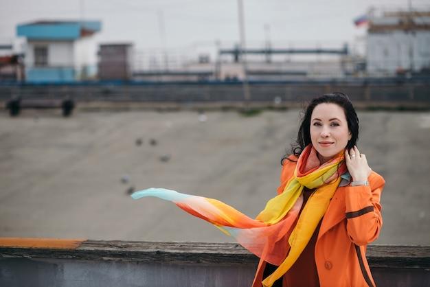 Fröhliches porträt des herrlichen mädchens mit dem schwarzen lockigen haar im orangefarbenen umhang und im bunten hellen schal.