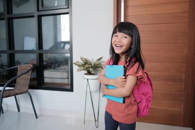 Fröhliches porträt eines schönen asiatischen grundschülers, der morgens allein zur schule geht