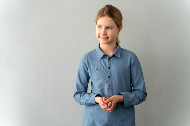 Fröhliches, positives kleines mädchen in einem blauen hemd an einer grauen wand