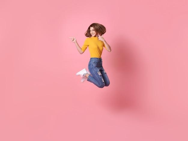 Fröhliches positives mädchen, das mit erhobener hand in die luft springt und auf den kopierraum zeigt, der auf rosafarbenem hintergrund isoliert ist